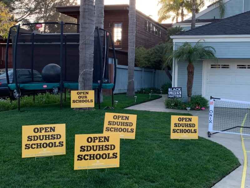 Signs urging school reopening