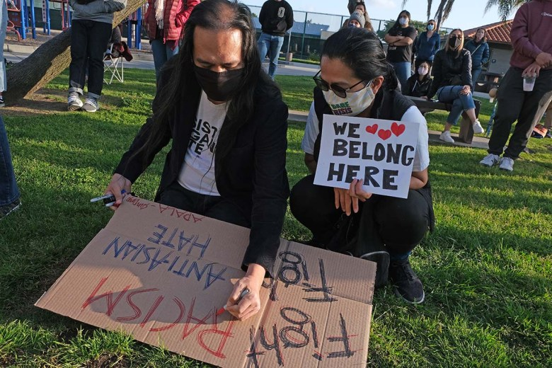 Asian Americans at the prayer vigil prepared signs.