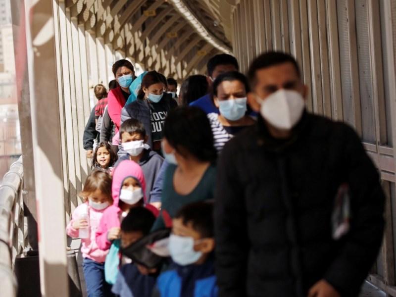 Migrants walk back to Mexico on border bridge