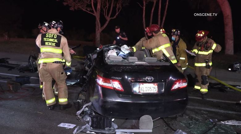 Firefighters examine badly damaged Toyota