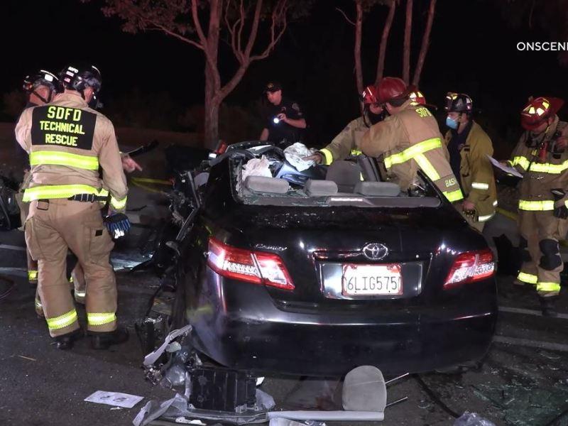 Firefighters examine badly damaged Toyota