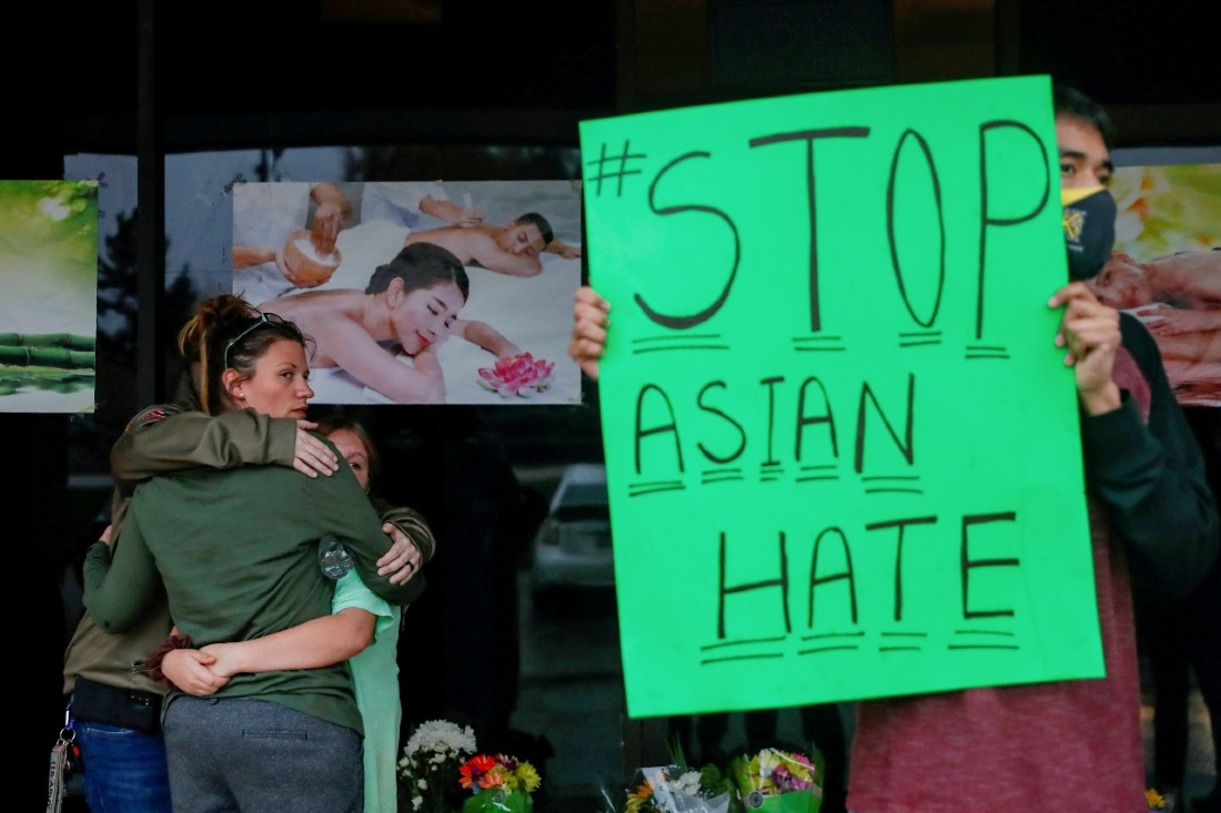 A man holds a site protesting hate crime