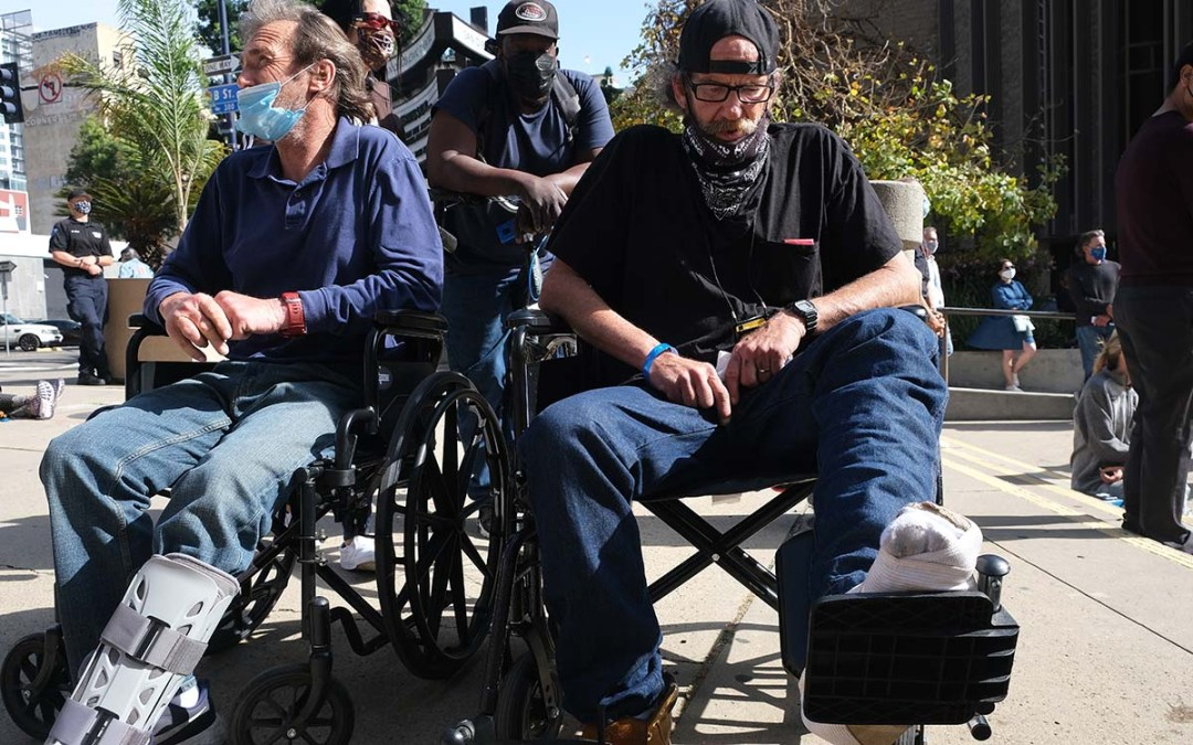 Attendees at a downtown memorial service, Duane Crawford (left) and Jesse Andrys, both had their legs broken in the car crash that killed three others. Photo by Chris Stone