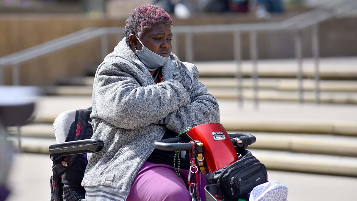 Amber Joseph, a friend of one of the three homeless men who died in a car crash, listens to an interfaith memorial service.