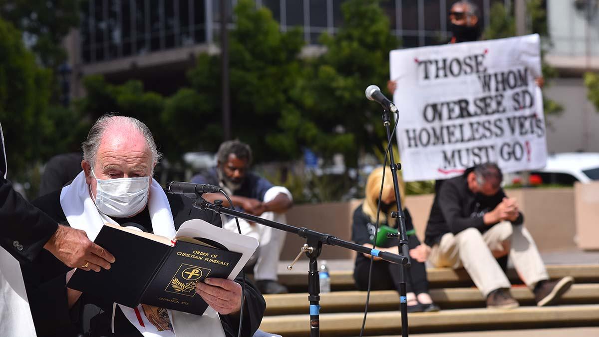 The Rev. Joe Carroll recites a prayer at an interfaith memorial service in downtown San Diego.