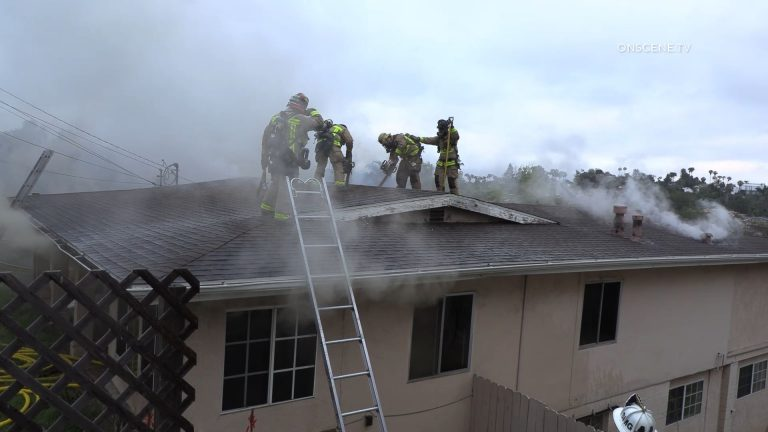 Firefighters on roof of burning home