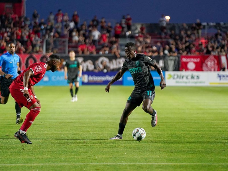 Loyal forward Tumi Moshobane (center) advances the ball during the 2021 season opener with Phoenix Rising in Wild Horse Pass Stadium in Chandler. Photo courtesy of San Diego Loyal
