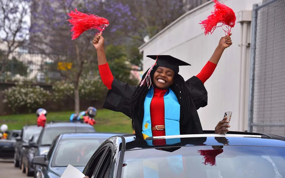 Elbers Katula, a social work major, shows she gave it the old college try as she graduates from City College. Photo by Chris Stone