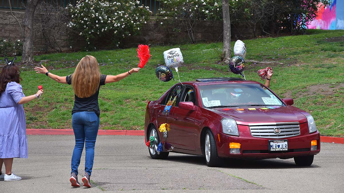 Professors and staff greet graduates in their decorated cars at San Diego City College. Photo by Chris Stone