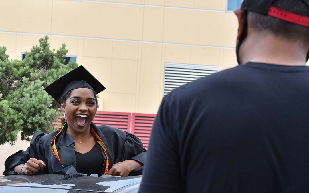 Graduate Jade Benn, a journalism student, reacts to college employee Cesar Gumapas, who announced students' names. Photo by Chris Stone