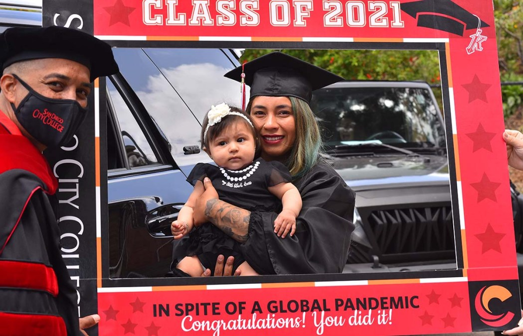 Brianna Maza, a special education major, poses with her 6-month-old daughter Leah while college president Ricky Shabazz looks on. Photo by Chris Stone