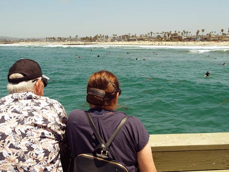 People enjoyed watching the waves and surfers from the newly reopened Ocean Beach Pier. Photo by Chris Stone