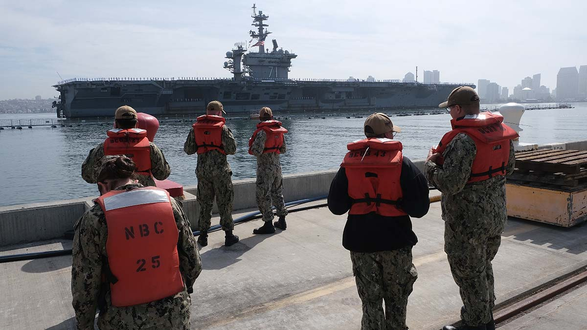 Crew members from the USS Carl Vinson stand by to help moor the USS Theodore Roosevelt. Photo by Chris Stone