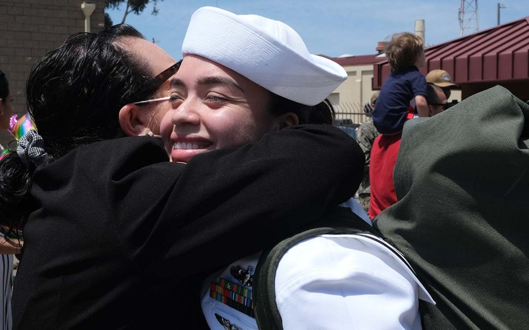 A sailor receives a hug upon returning to San Diego. Photo by Chris Stone