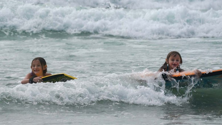 Young girls enjoy the surf at La Jolla Shores. Photo by Chris Stone