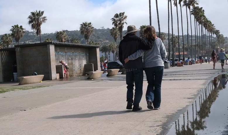 A couple strolls along the sidewalk at La Jolla Shores. Photo by Chris Stone