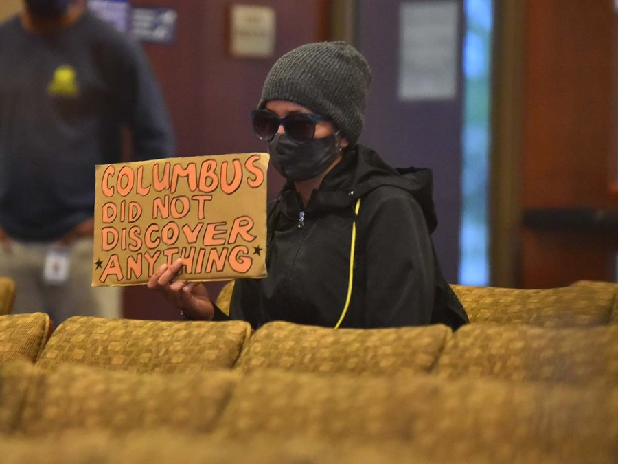 Speaker displayed a sign summarizing belief about Columbus.