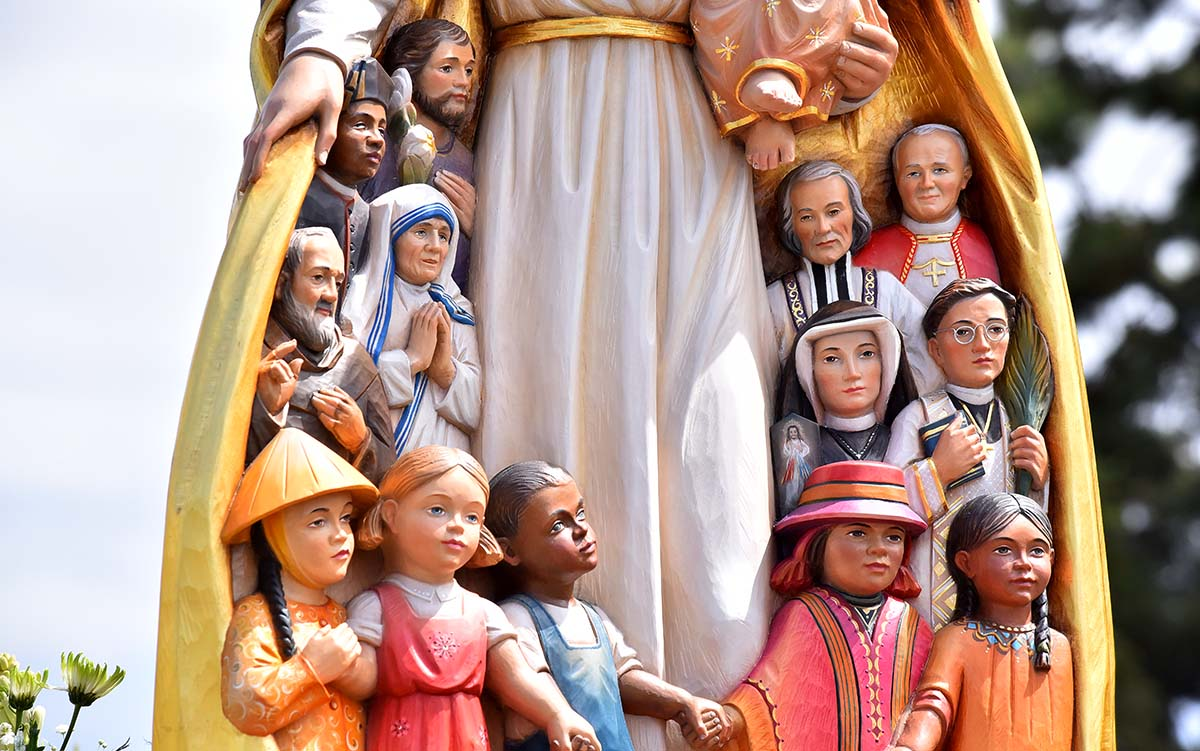 """The """"Mary, Mother of the Church"""" statute depicts well-known saints. an children of different nations at the bottom. Photo by Chris Stone"""