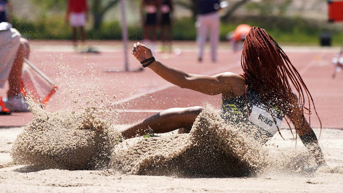 Quanesha Burks hair envelopes her in the long jump. Photo by Chris Stone