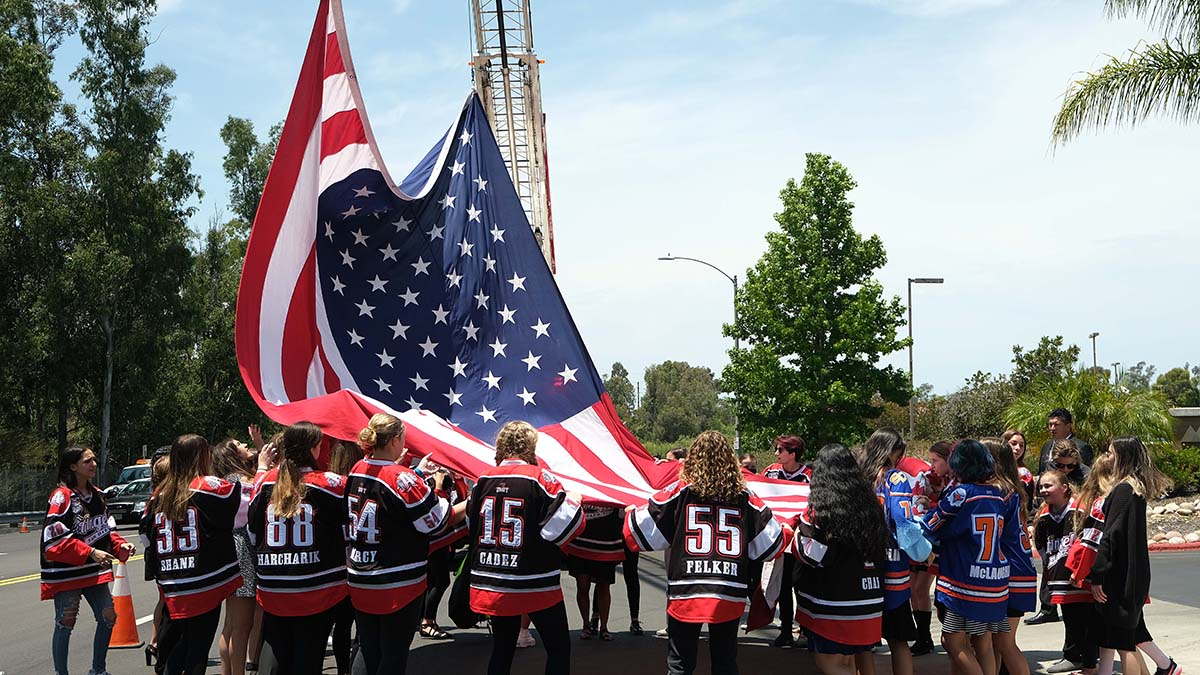 Members of the San Diego Angels hockey team retrieve a flag given to them by the fire department. Photo by Chris Stone