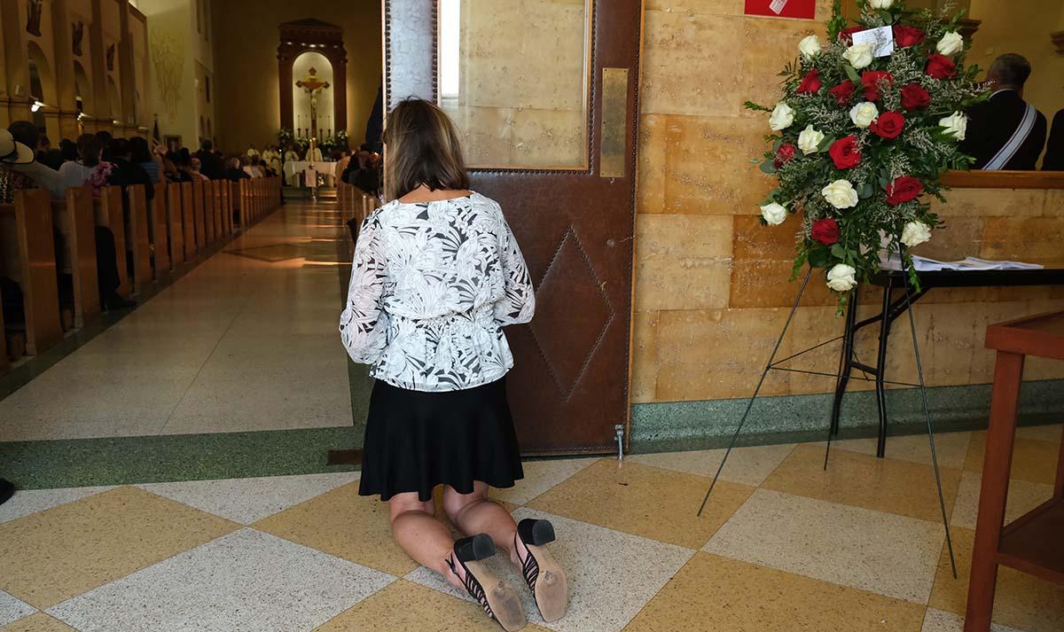 A woman kneels near a floral wreath for Fr. Joe Carroll.