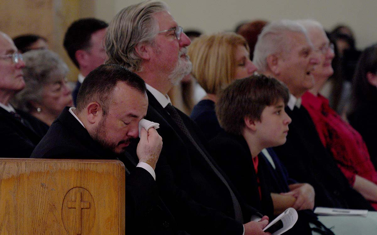 Jose Gonzalez, personal assistant for Fr. Joe Carroll, (left) wipes away a tear.