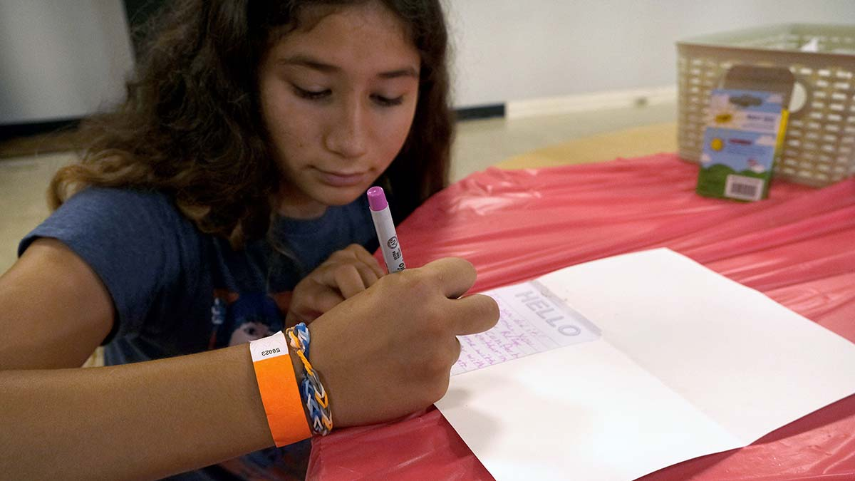 Melissa Rodriguez, 12, writes a welcome note for the My First Home project. Photo by Chris Stone
