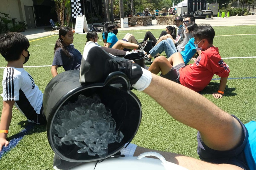 Youth compete in the Cold Feet challenge in which they passed on ice buckets with their feet. Photo by Chris Stone