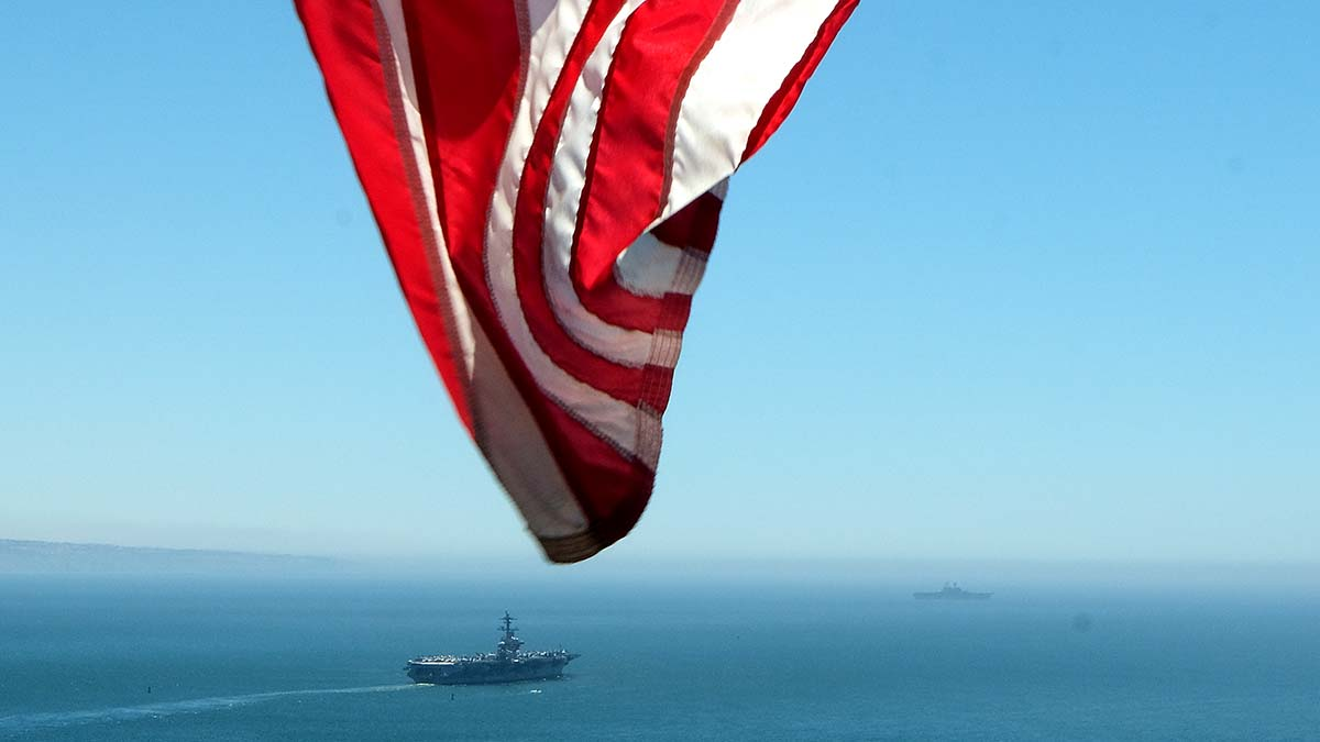 A relative flies an American flag as the USS Carl Vinson heads off on a deployment. Photo by Chris Stone