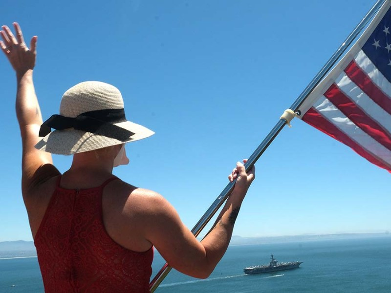 Family members flew flags and waved goodbye to loved ones aboard the USS Carl Vinson. Photo by Chris Stone