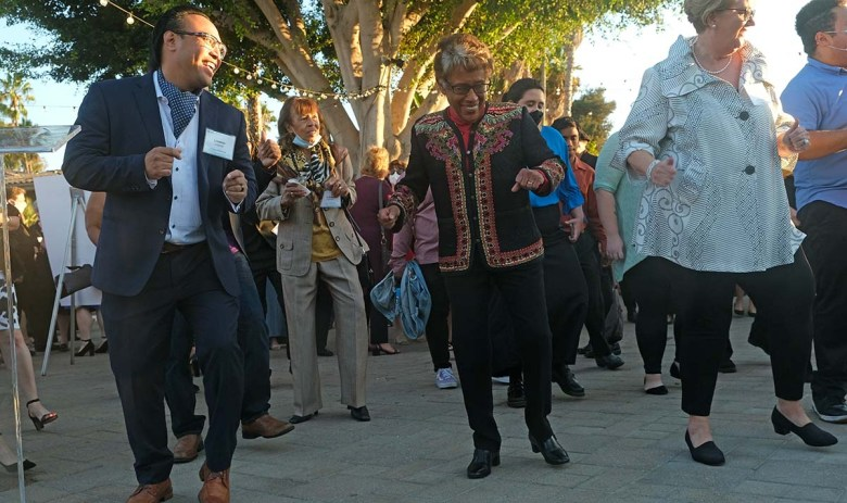Former SDCCD Chancellor Constance Carroll (center) dances the Electric Slide with guests. Photo by Chris Stone