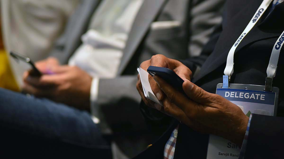 Delegates at election-law panel study their smart phones.