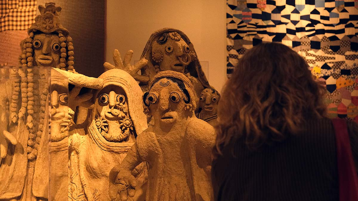 A visitor observes the Mithilia Figures from India at the reopened Mingei International Museum. Photo by Chris Stone
