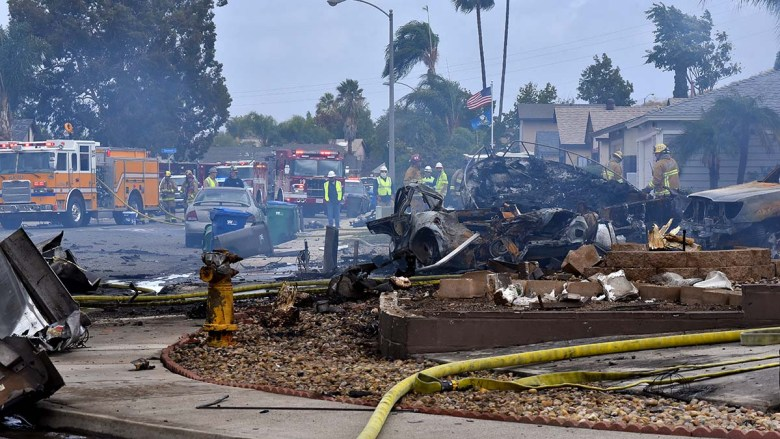 Firefighters mop up after extinguishing flames of two houses burned in a plane crash. Photo by Chris Stone