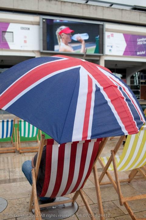Man under large Union flag umbrella in deckchair at Millennium Square, Bristol.