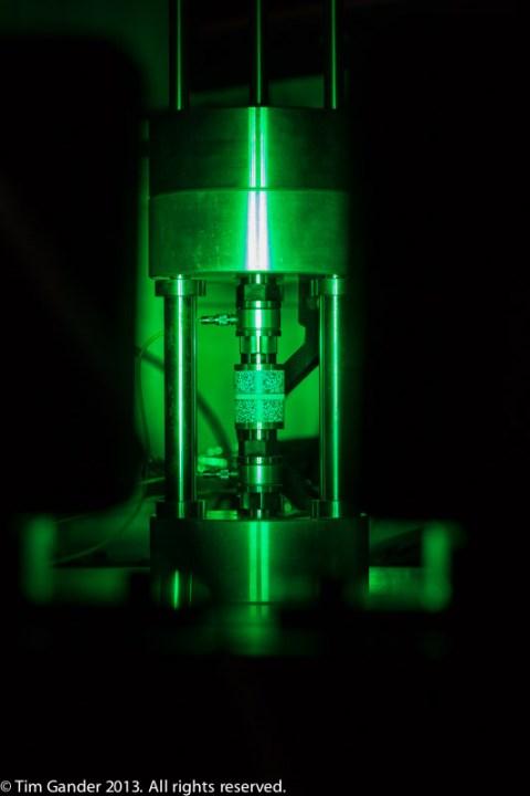 A scientific instrument glows green in a dark surrounding
