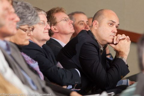 A group of seated business people in an auditorium listen to a presentation as one man leans forward to hear better