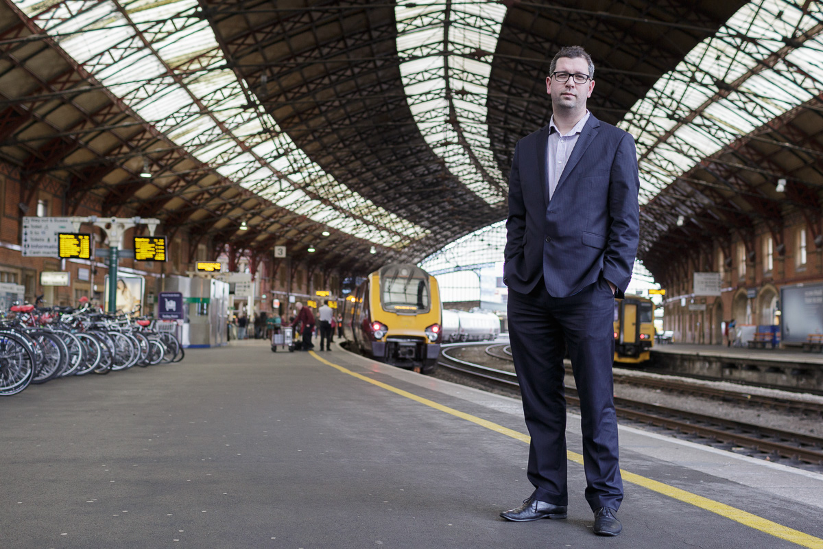 Profile photo of Dan Panes of First Great Western stands on Platform 1 at Bristol Temple Meads station with the station canopy, engine and passengers visible in the background.
