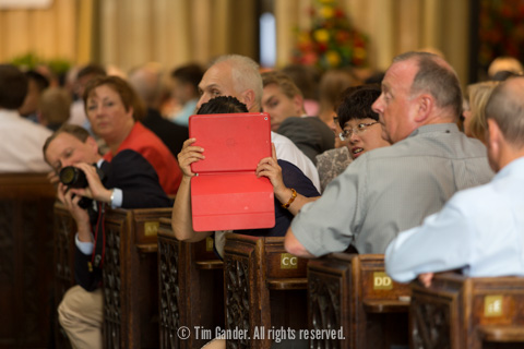 A parent using an iPad inside the abbey to photograph the ceremony