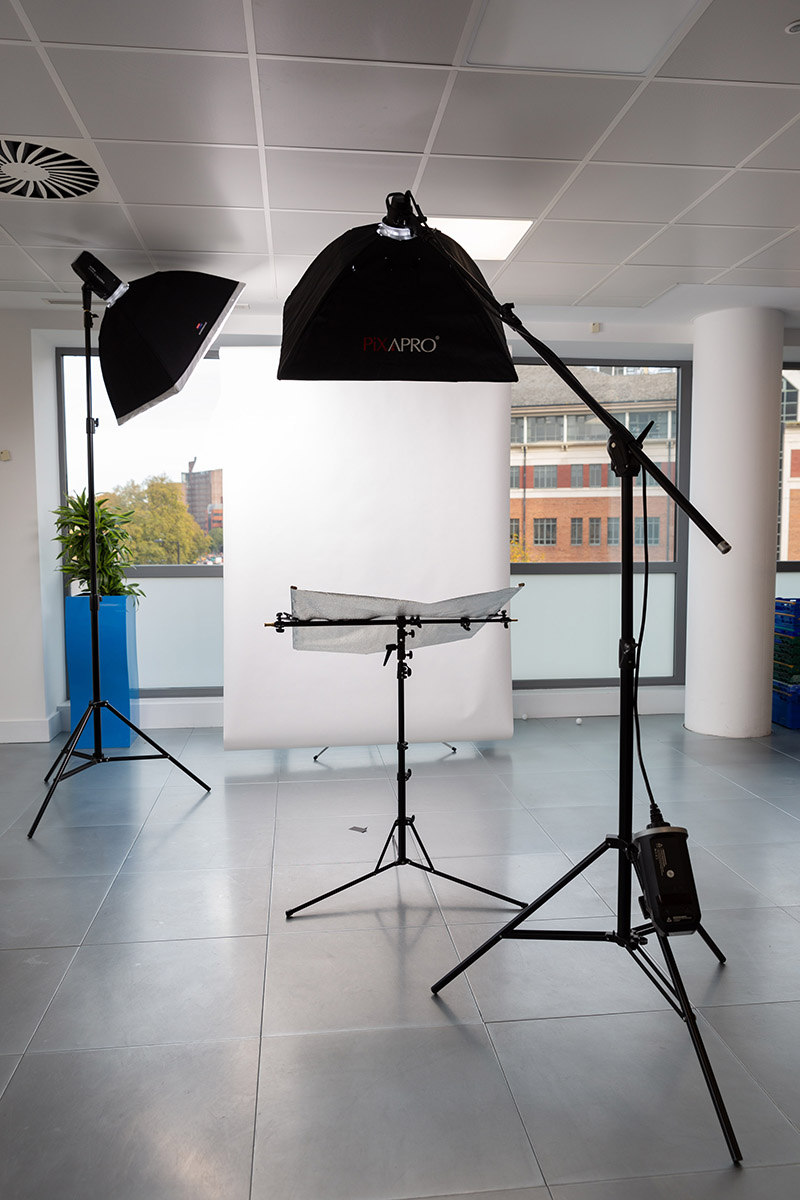 A portable photographic studio lighting setup in a client office space.