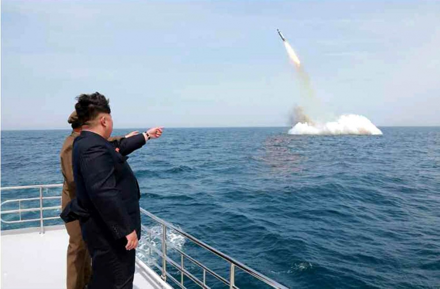 Photo purports to show Kim Jong Un standing by a ship's rail at sea pointing to a missile launching from the water. A fake photo.