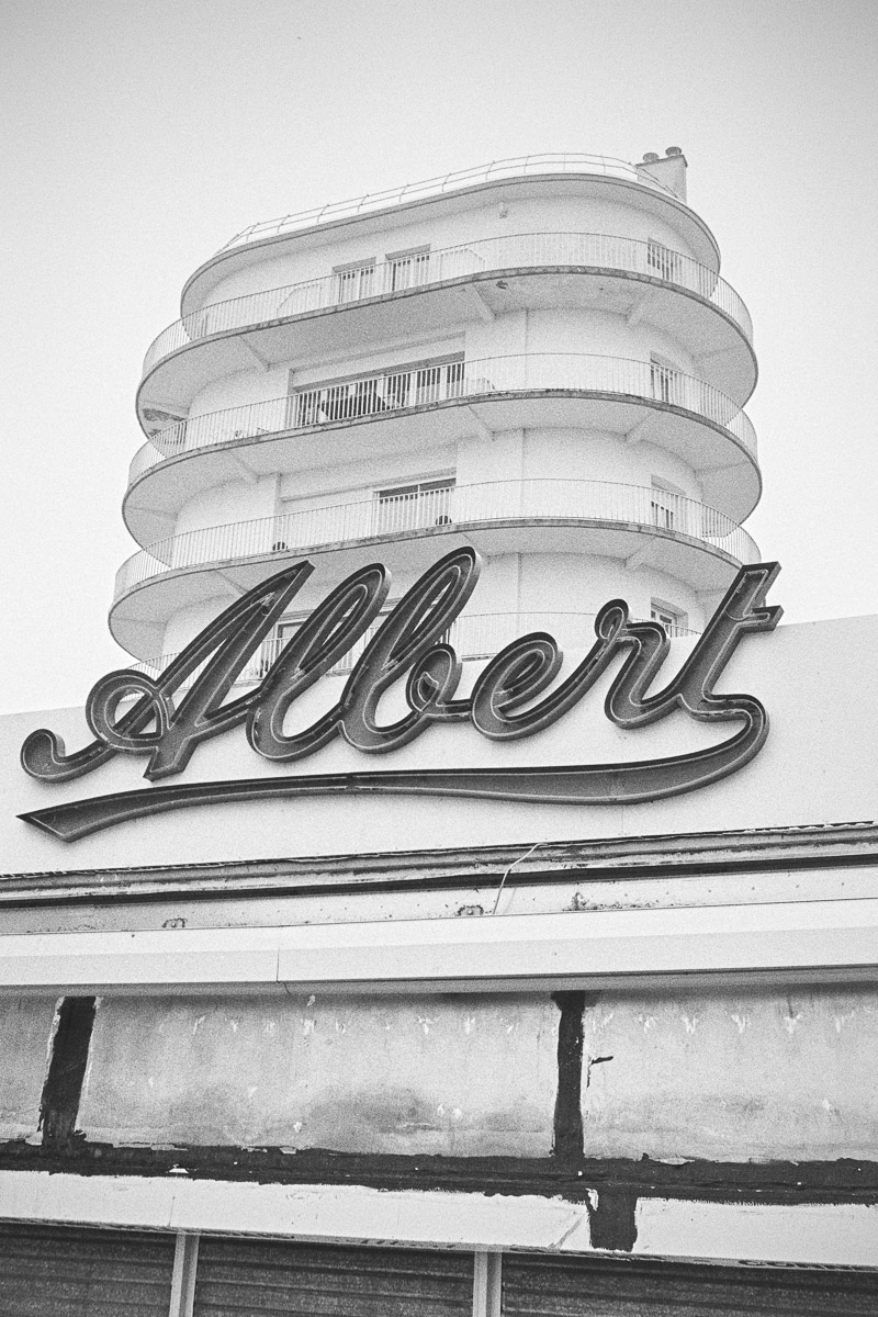 An Art Deco building rises up behind a large neon sign which says Albert in a handwritten-style font.