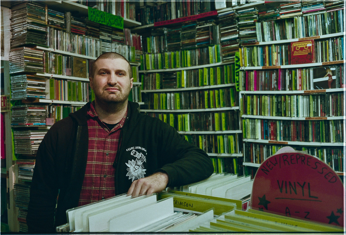 Portrait of manager of Raves from the Grave Tom Coates surrounded by records and CDs.