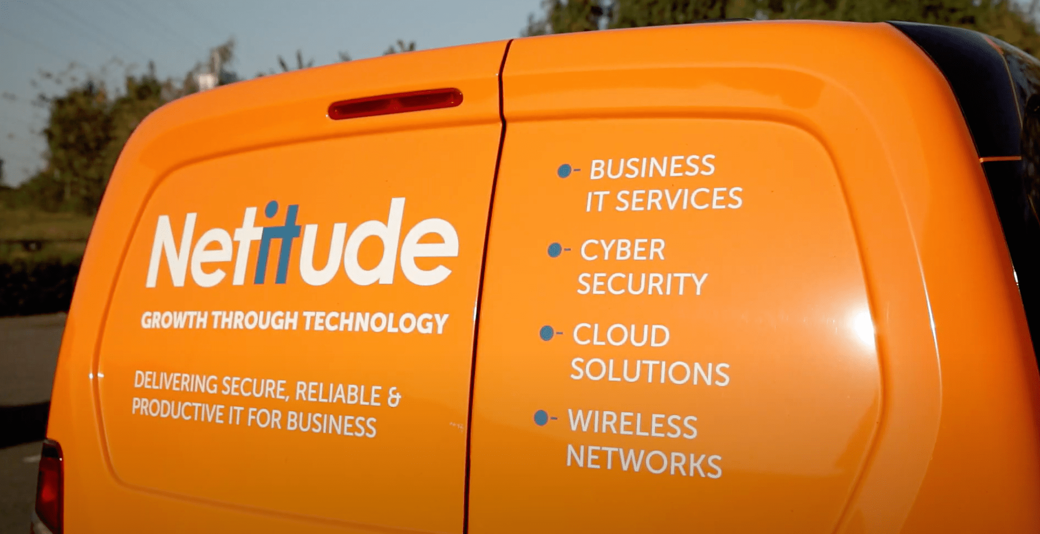 Still from Netitude video showing the rear door text of a Netitude van.