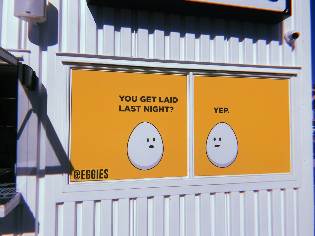 "Sign of an egg that says to another ""you get laid last night?"" The other responds, ""Yep""."