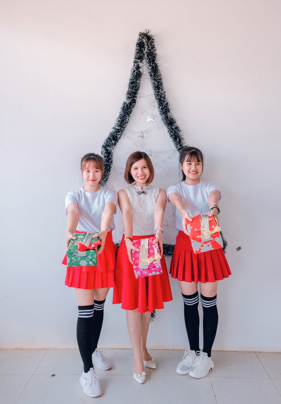 three women standing holding gift boxes