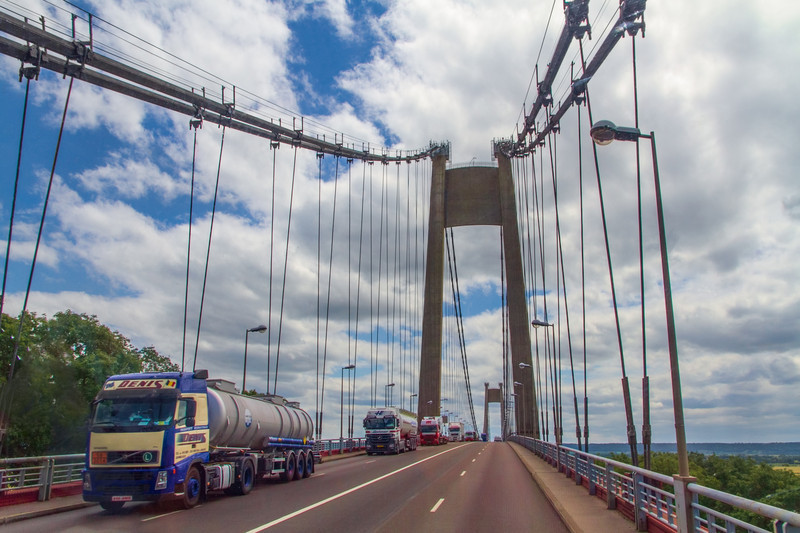 These trucks are traveling over a large bridge in France, outside of Paris. All the cars are smaller than in the US, except the trucks and buses.