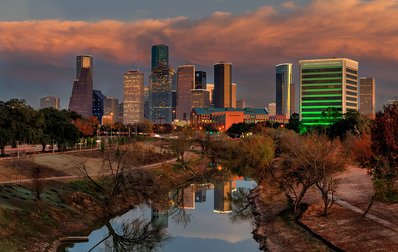 At sunset, the buildings come alive in colors and lights. This view over Buffalo Bayou is looking east, towards the west side of downtown Houston. Photo by Tim Stanley Photography.