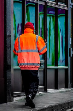 A man wearing an orange reflective jacket.