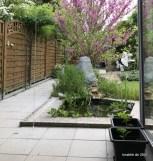 Blick von der Terrasse auf Teich und Judasbaum